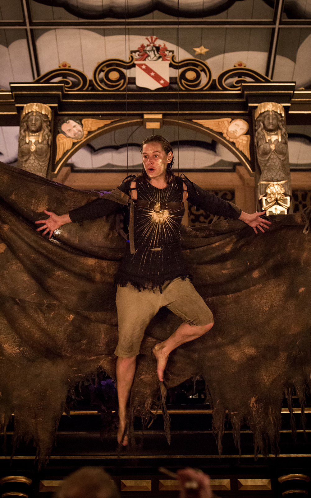 A woman with large wings and a painted gold face, hangs in the air of the Sam Wanamaker Playhouse