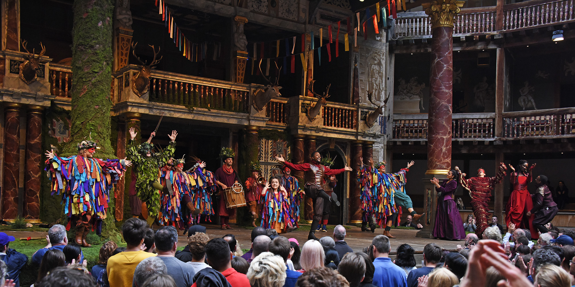 A group of actors wearing brightly coloured costumes dance on the Globe Theatre stage.