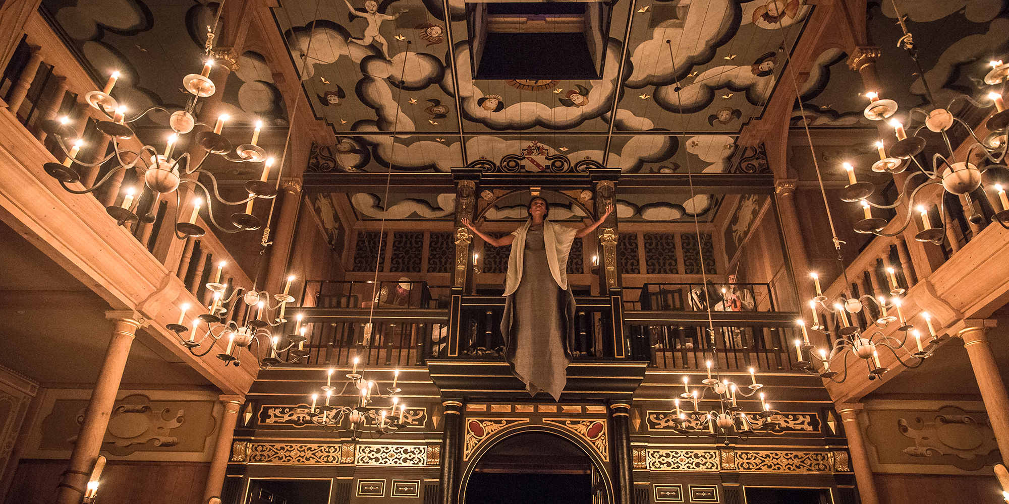 A woman descends from a trapdoor in the painted heavens of the Sam Wanamaker Playhouse, which is lit by candlelight