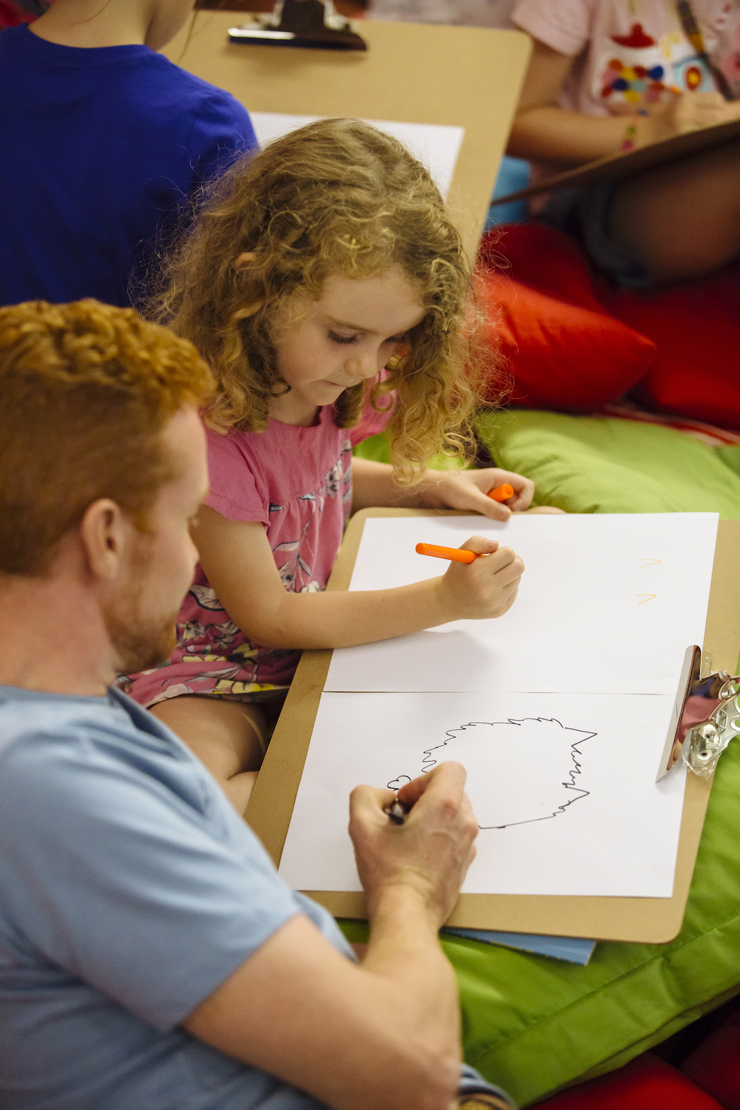 A man helps his daughter draw on a piece of paper