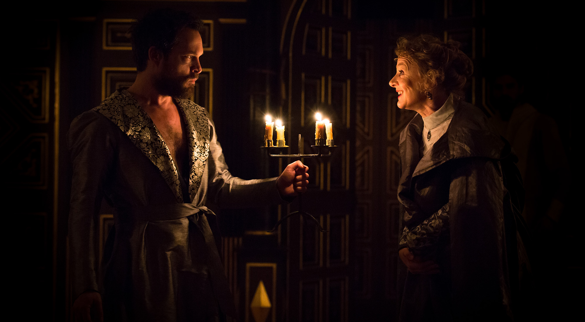 A man wearing a dressing robe holds a lit candelabra before a woman who smiles at him.