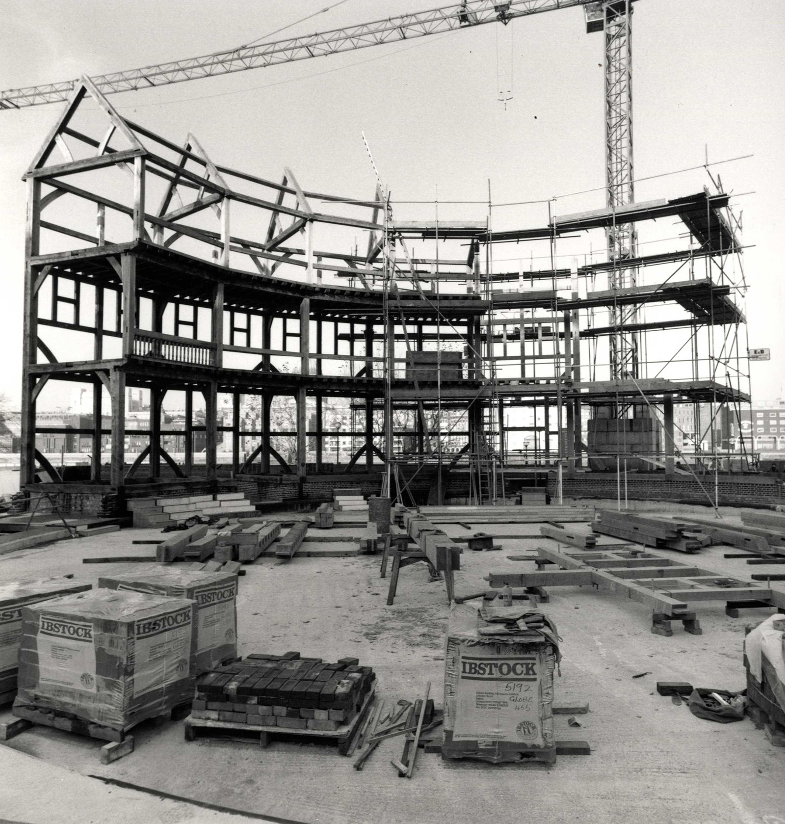 A timber circular structure starts to take shape on a construction site, with a crane in the background.