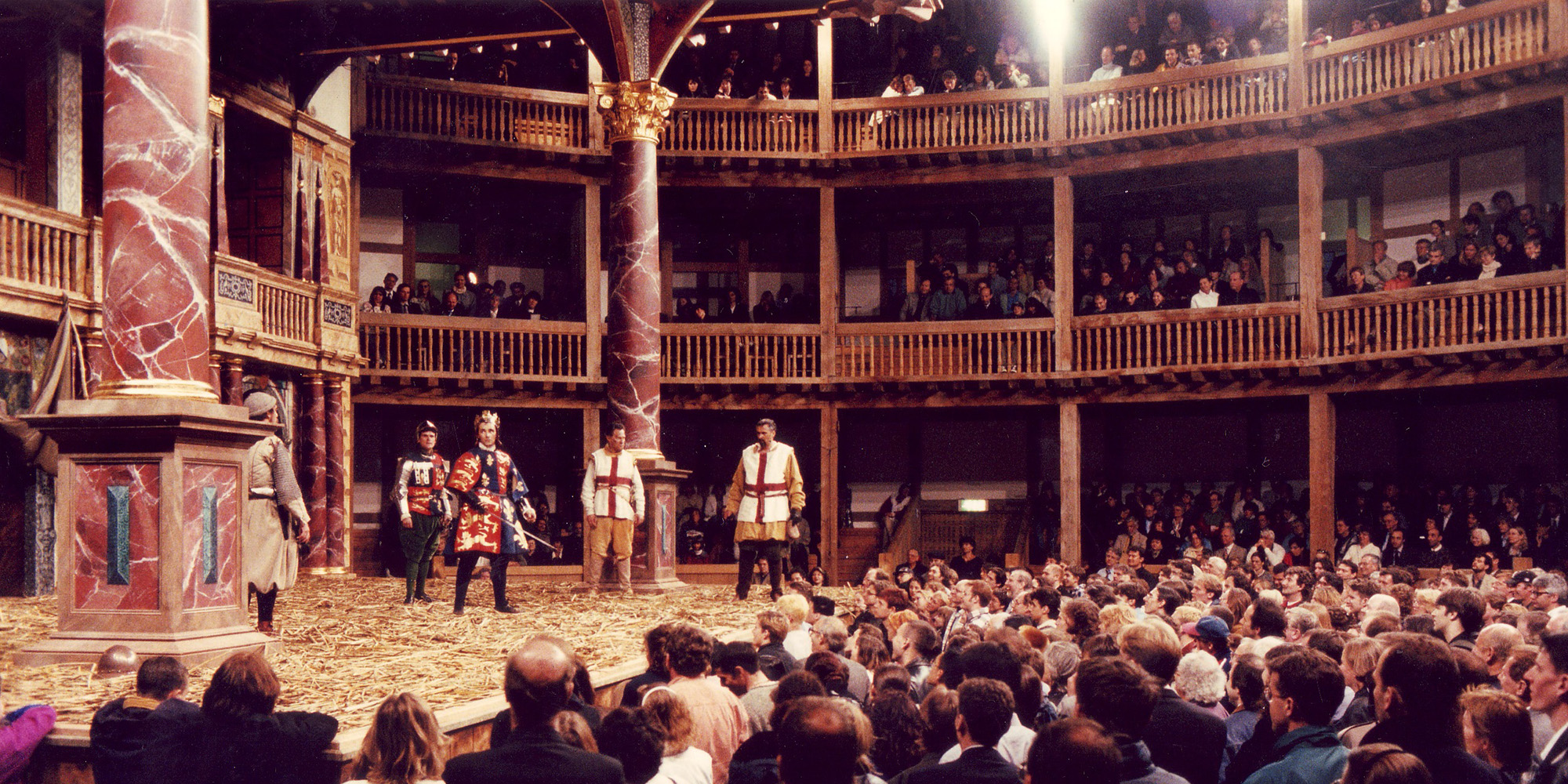 A large crowd of audience members stand watching a play in a circular timber structure.
