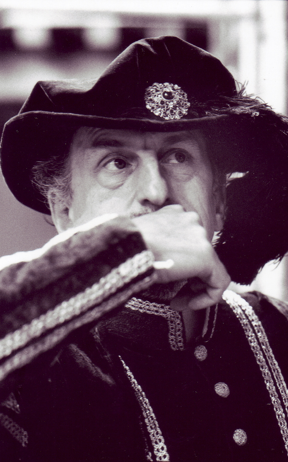 A man wearing a large hat leans his hand to his mouth.
