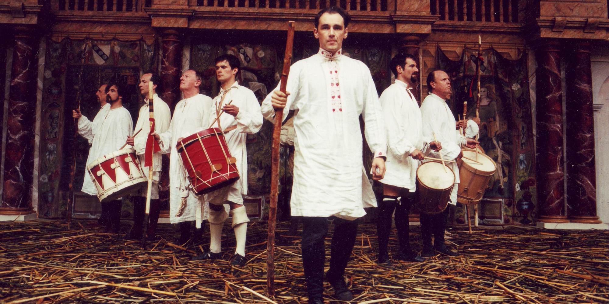 A group of actors wearing white tunics stand in a v-formation on a stage covered in straw.