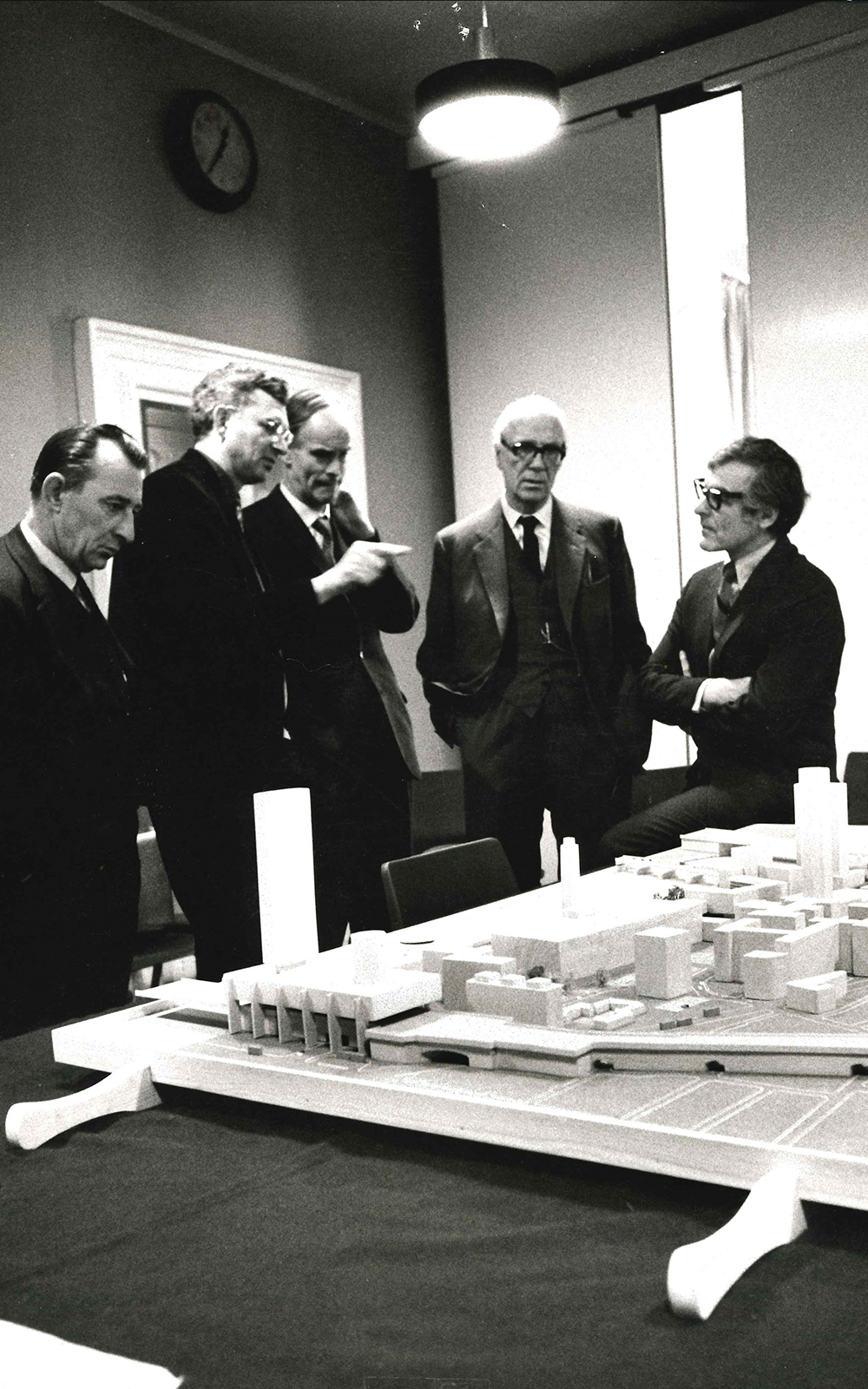 A group of men stand before a model plan of a development site.