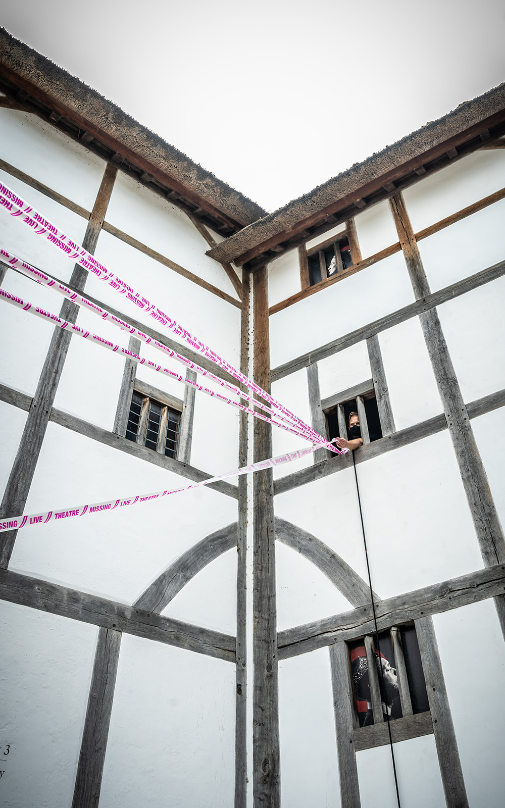 The white wattle and daub of a theatre wall, with white and pink tape crossing infront.