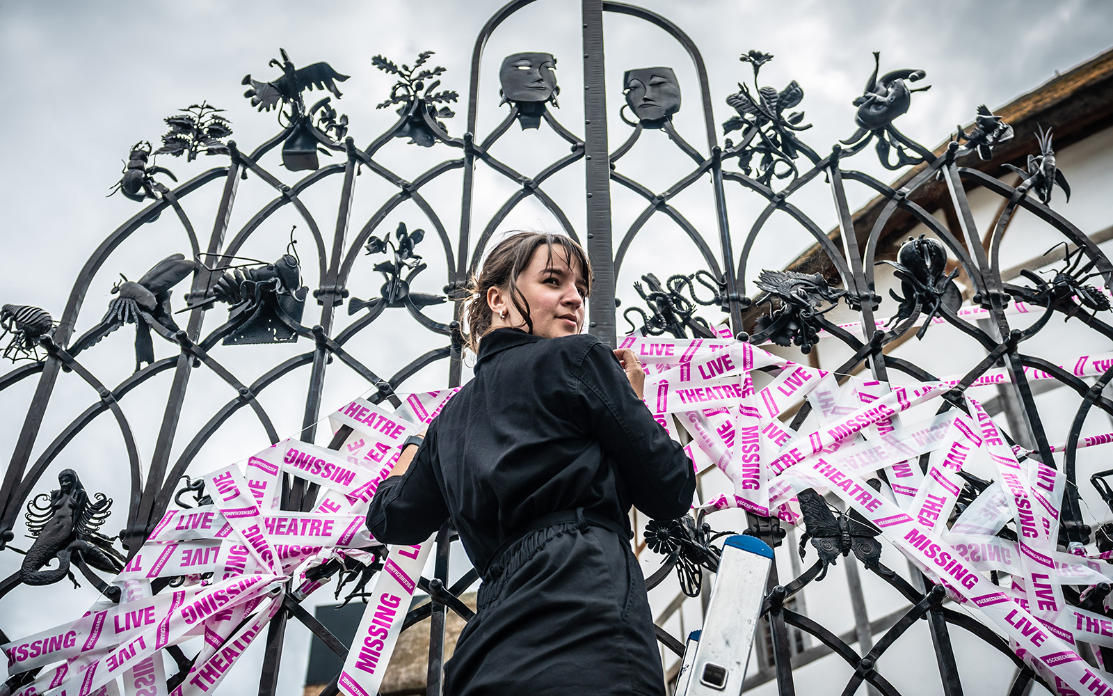 A shot looking up at a woman standing before a set of iron gates, placing white and pink tape.