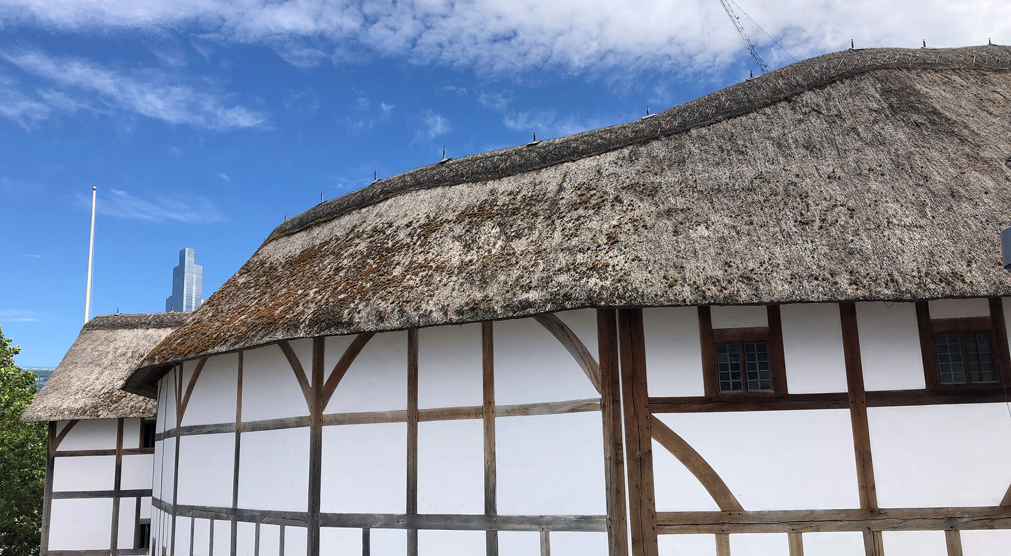 A side view looking at a white wattle and daub theatre, with a blue sky above.