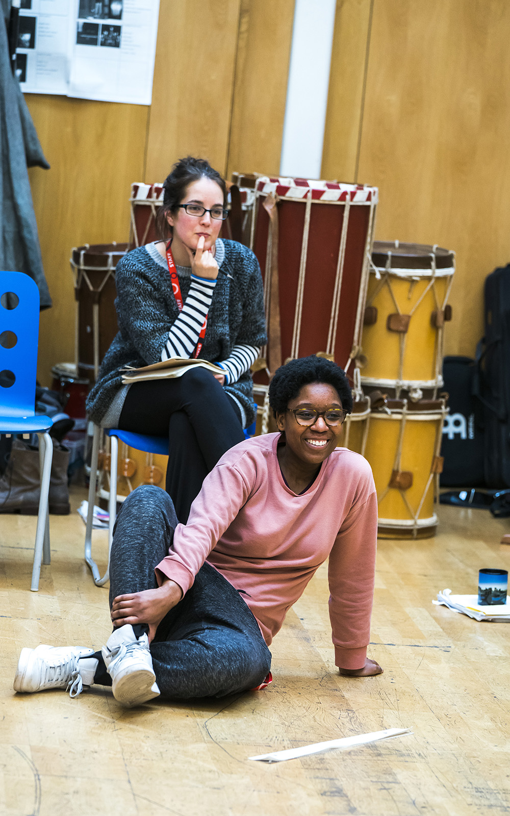 Two people are in a rehearsal, one is sat on a chair looking pensive, the other sits on the floor smiling
