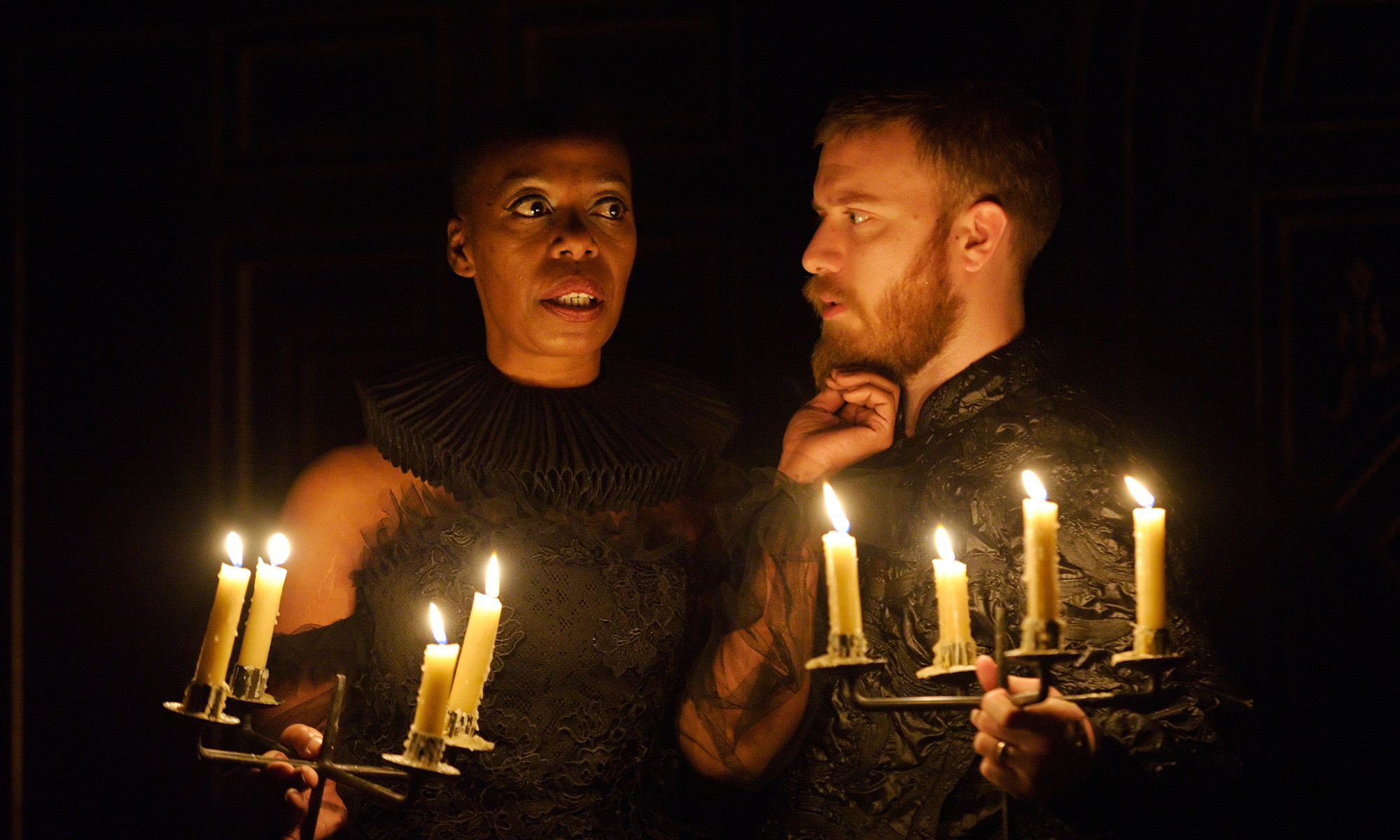 A woman and man stand in the glow of candlelight, the woman's hand touching the man's chin.