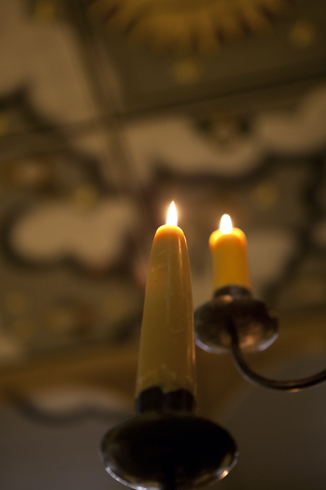 Two candles sit on a black candelabra