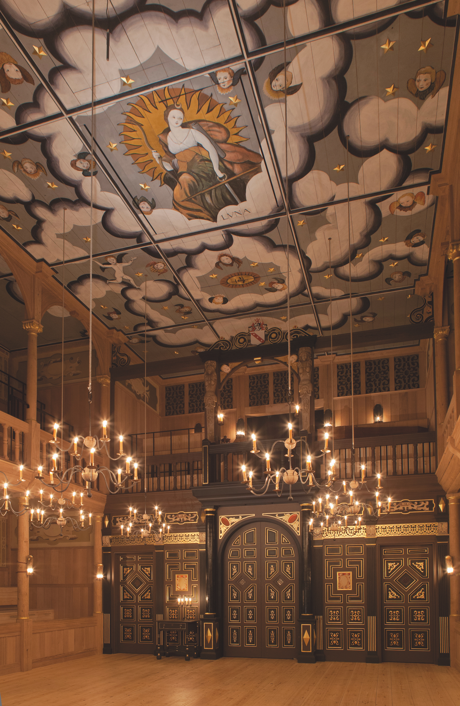 A tall ceilinged theatre with candelabras