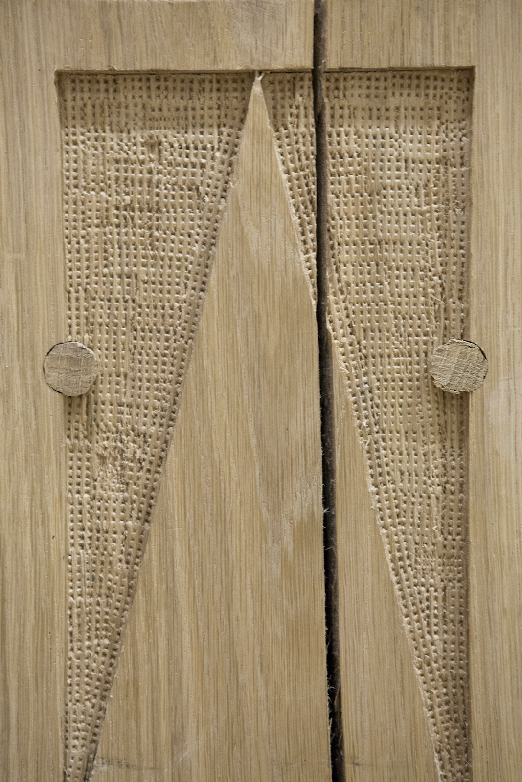 A close up of a wooden material with textured patterns carved into it