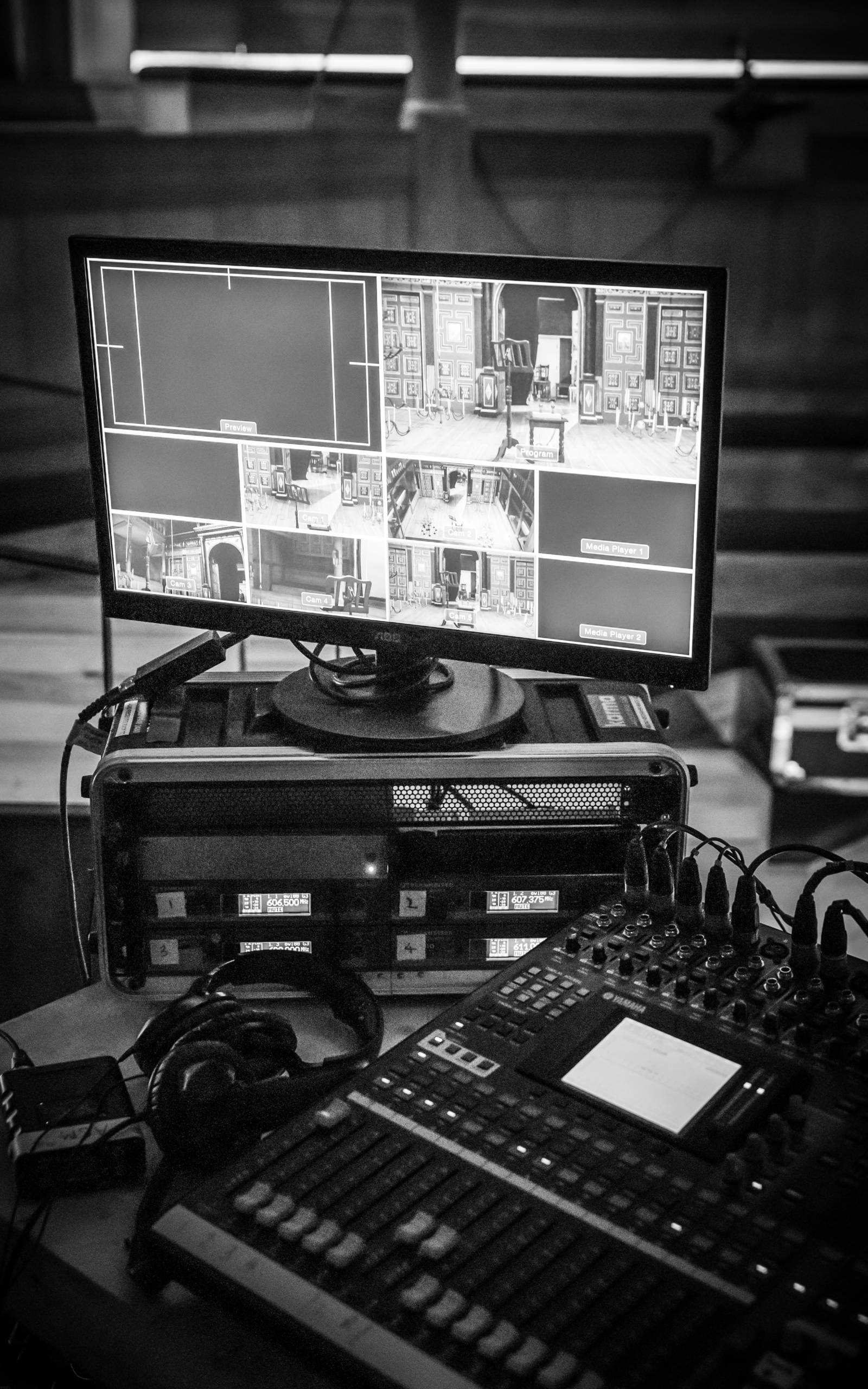A monochrome image of recording equipment and a screen showing different camera angles