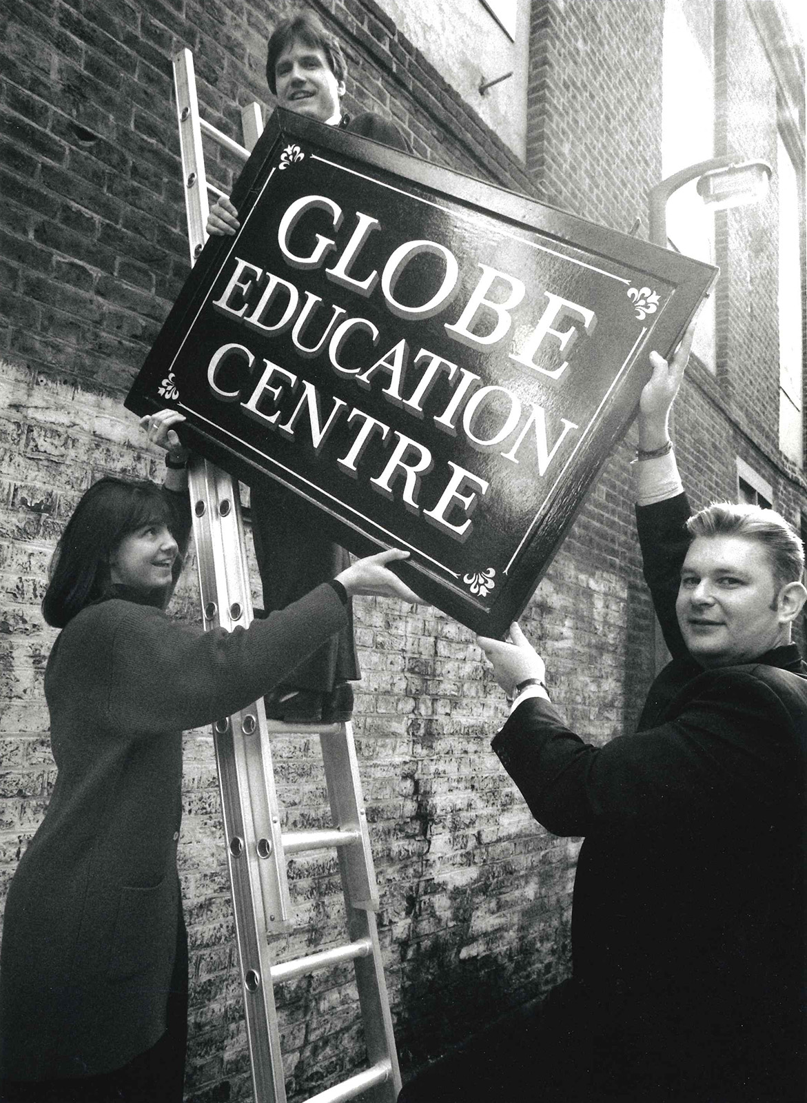 Three people lift a sign saying Globe Education Centre up a ladder.