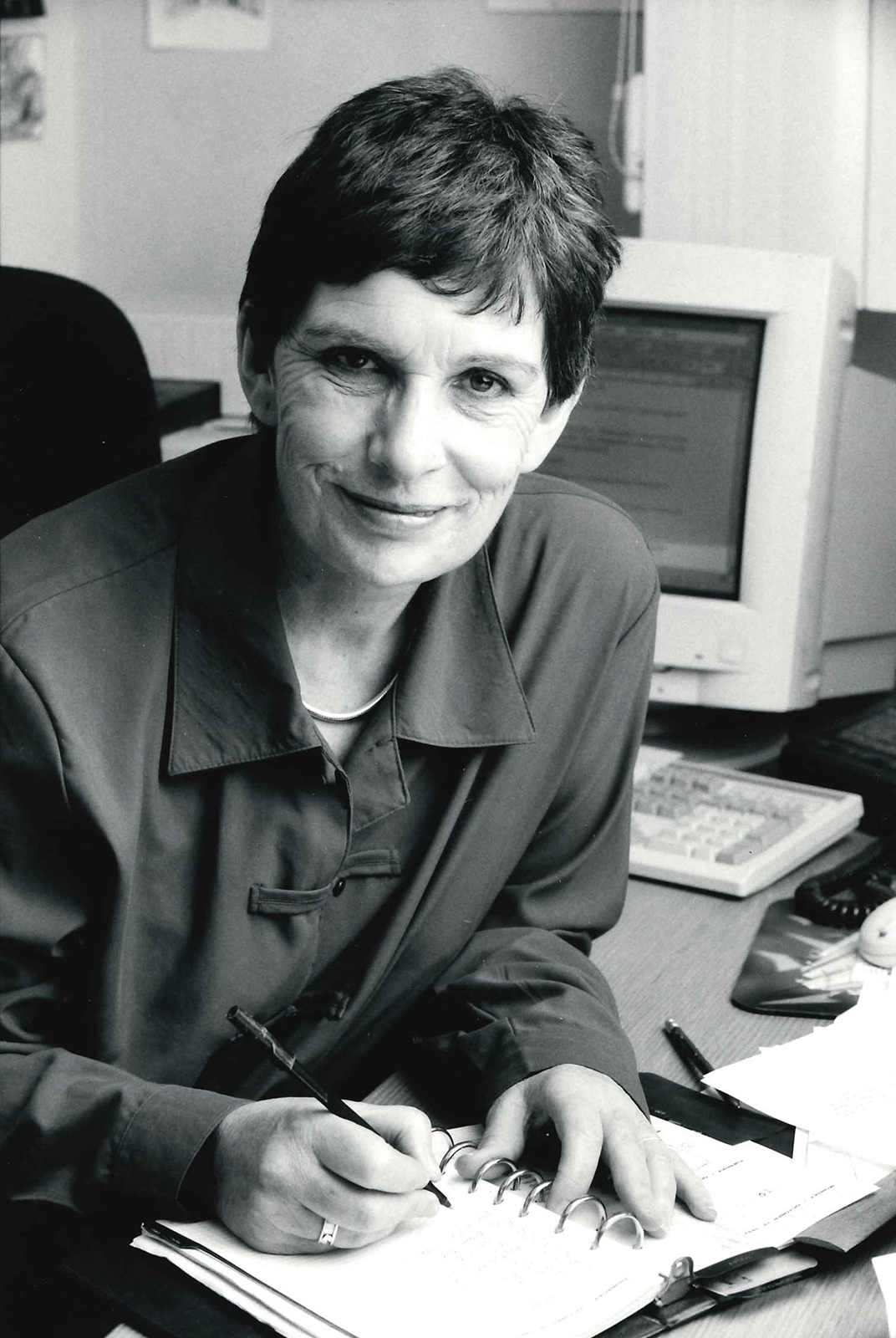 A black and white photograph of a woman smiling into the camera whilst writing in a notepad
