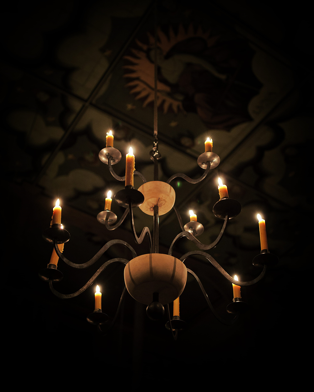 A view looking up at a lit candelabra, the painted ceiling above.