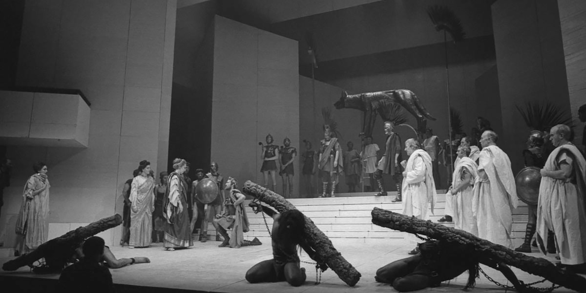 Black and white photograph of a proscenium stage, with a large group of actors standing in Roman garb: white tunics and robes, with plumed helmets.