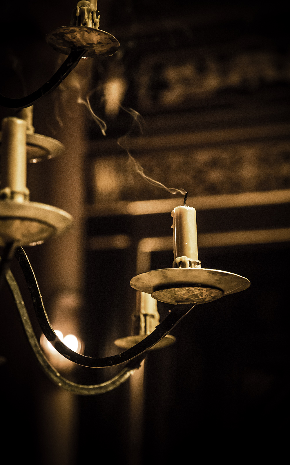 Smoke rises from a candle that has recently been extinguished.