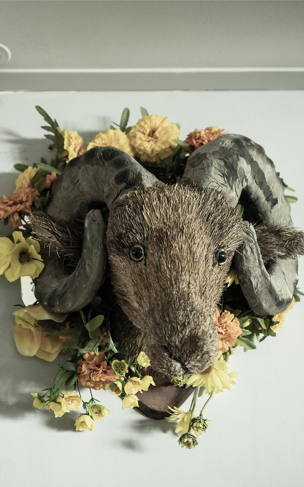 A head of a ram surrounded by flowers mounted on a wall