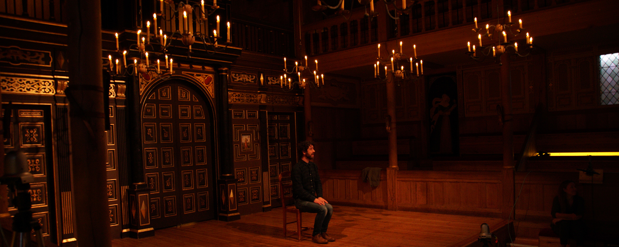 An actor sits on the stage surrounded by the candlelight of the indoor playhouse