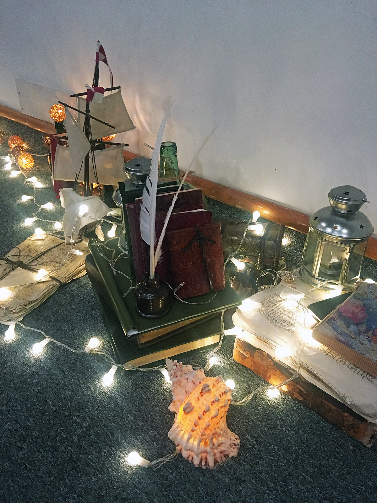 Fairy lights wrap around a pile of books, a model ship and lantern.