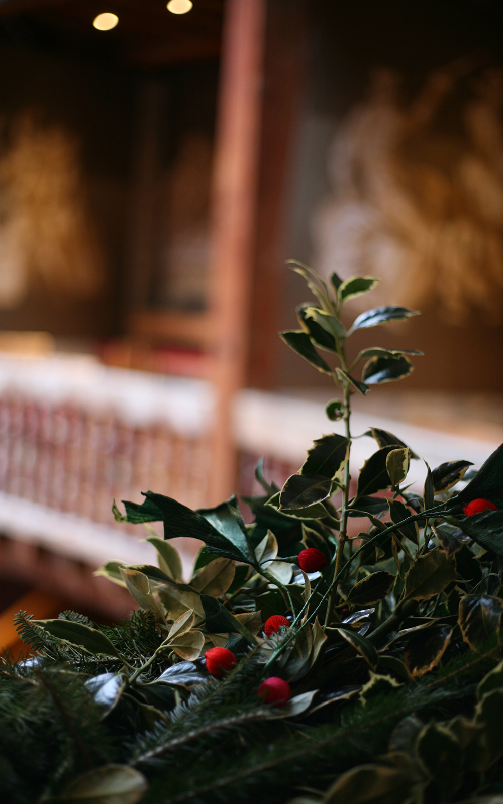 A close up of a holly wreath wrapped around wooden banisters.