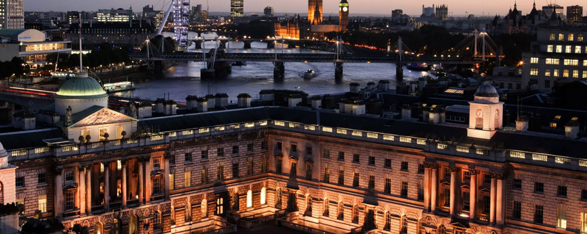 A wide nighttime shot of a large, white Neoclassical building, with the London skyline behind.