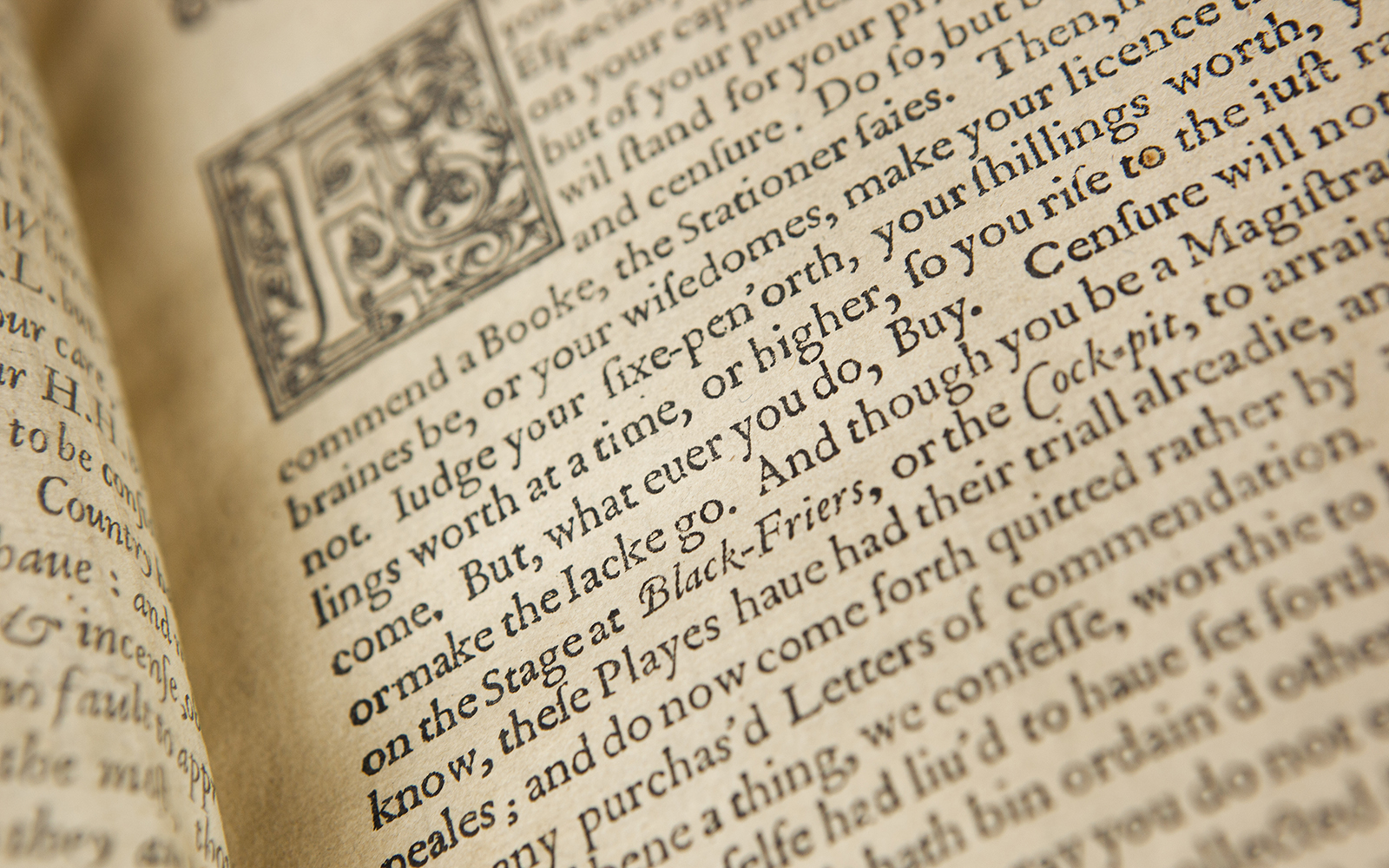 An old book lies open, with a floridly illustrated first letter