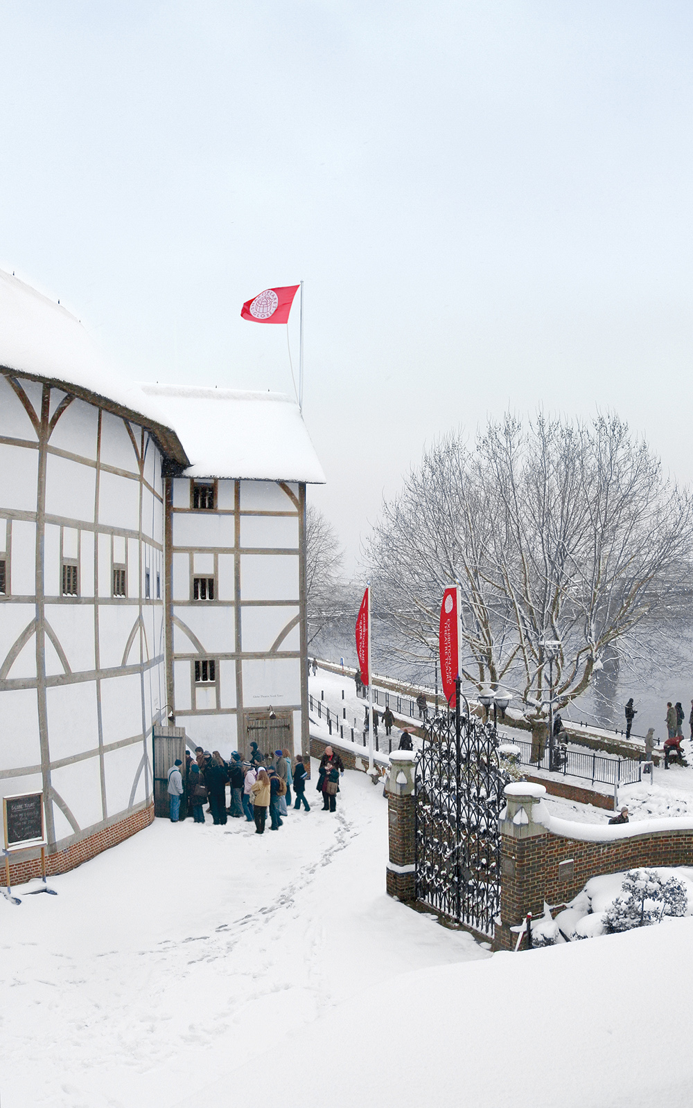A snowy view of the white circular timber structure theatre, with the bank of the River Thames infront