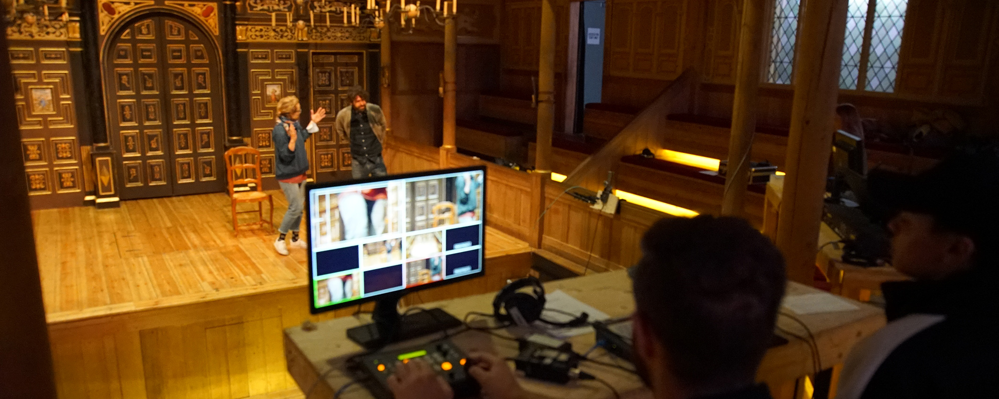 An image of the Sam Wanamaker PLayhouse with two actors rehearsing on the stage and a monitor showing different camera angles