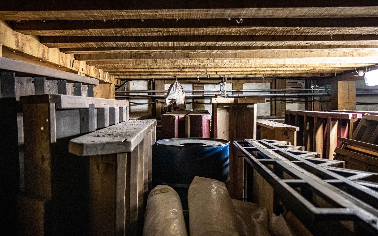 Items of wooden staging and barrels are stored in a basement room