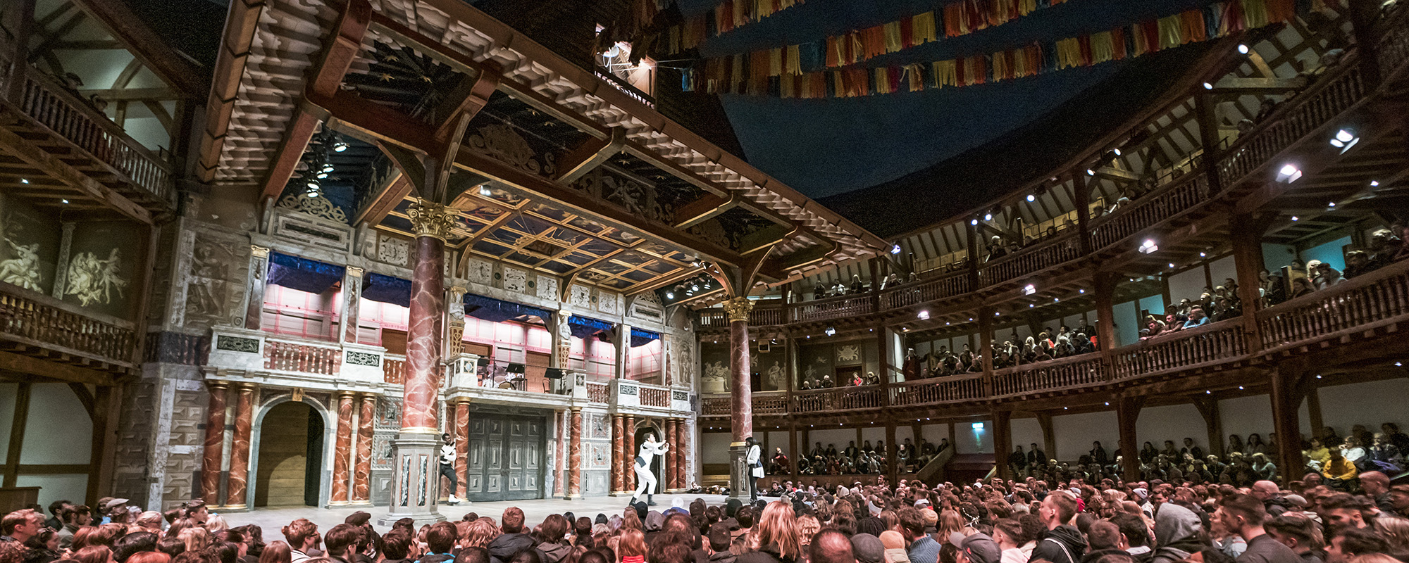A full audiences watches an actor on stage at nighttime in a circular wooden theatre.