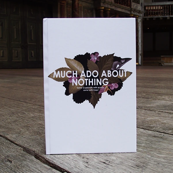 A white notebook with floral design and text reading: Much Ado About Nothing