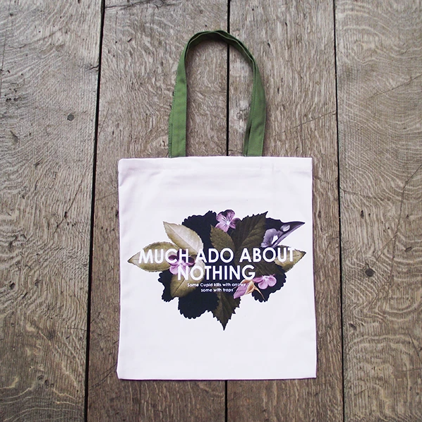 A white cloth tote bag with floral design and text reading: Much Ado About Nothing