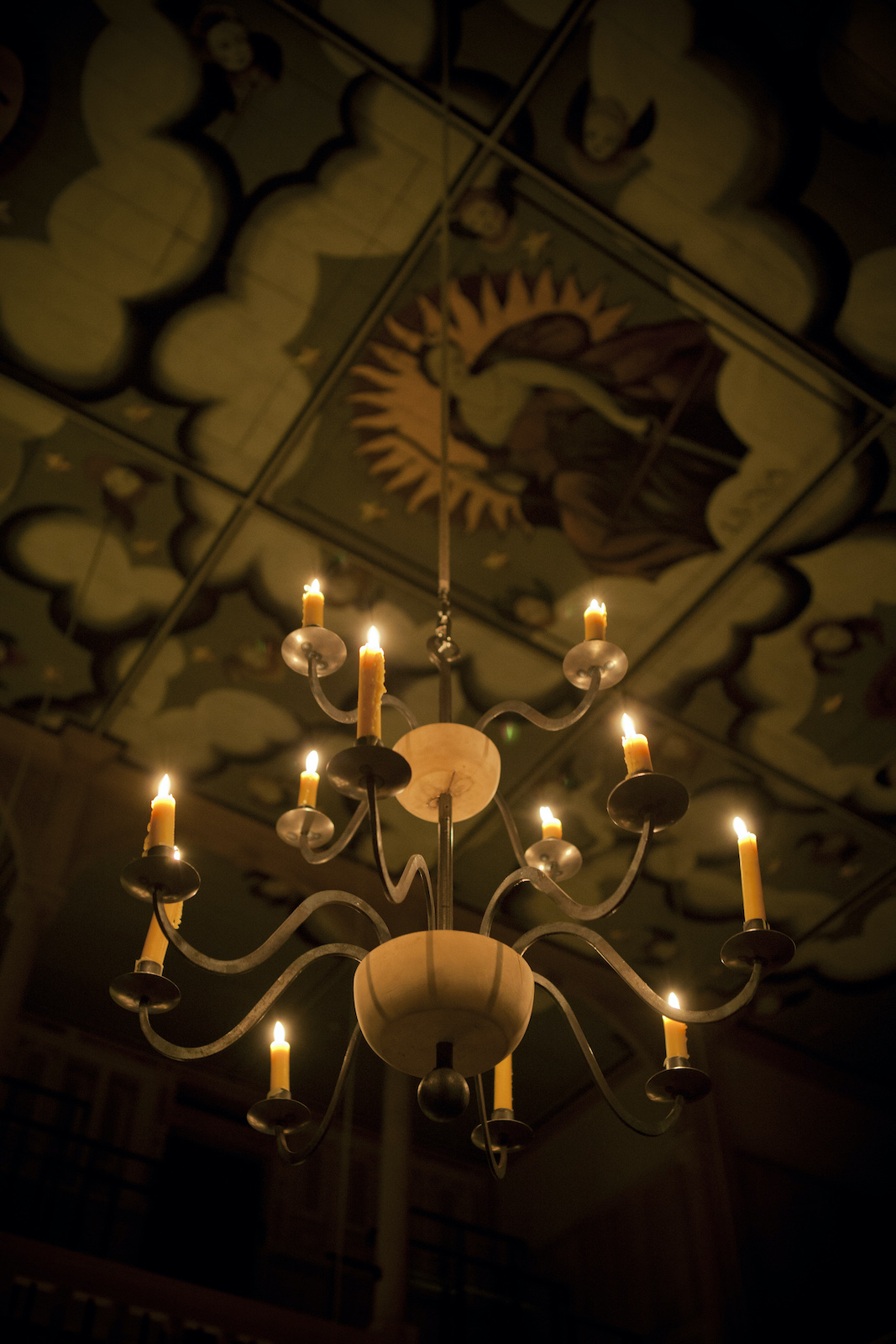 A lit candelabra hangs from a decorated ceiling.