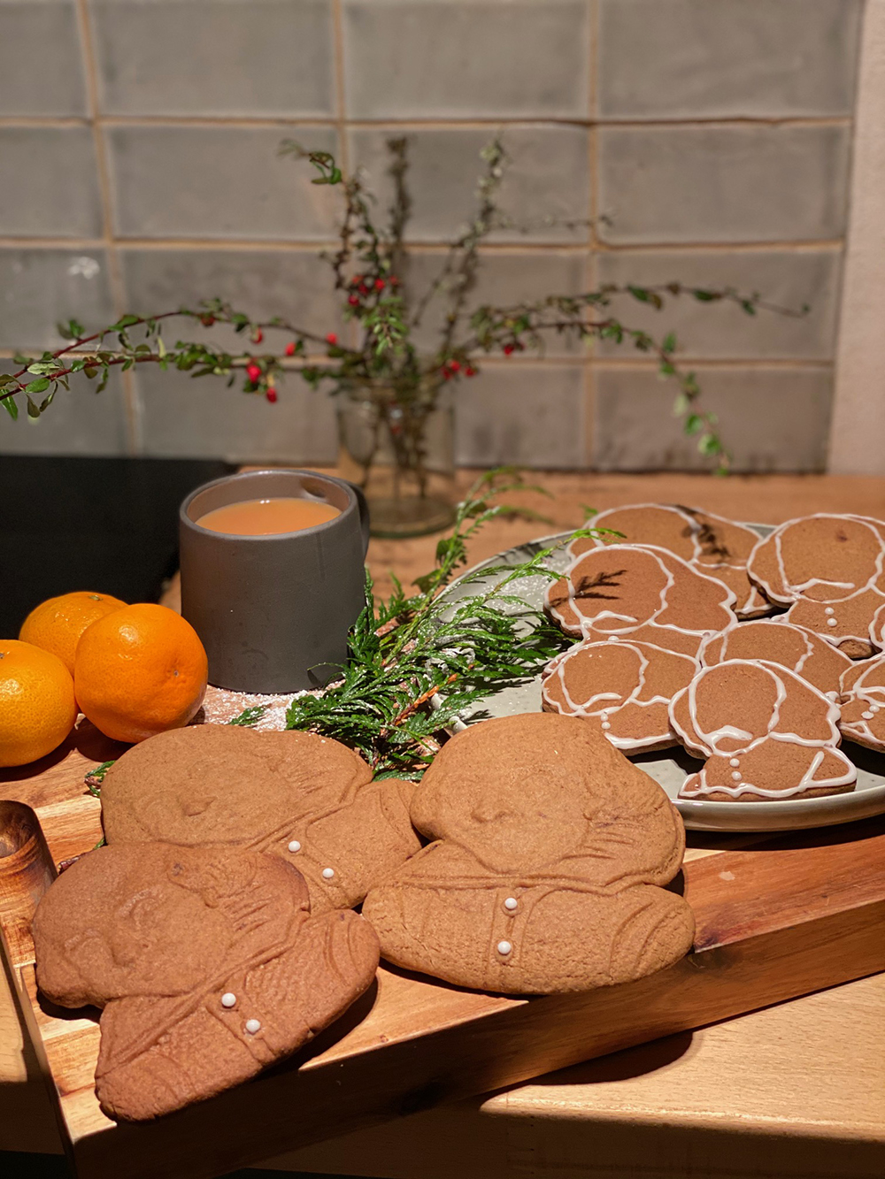 Gingerbread biscuits in the shape of Shakespeare's face rest on a plate with a mug of tea.