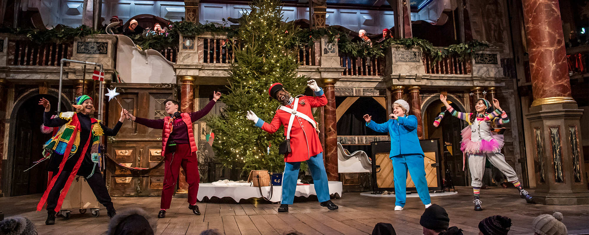 The cast of 'Christmas at the (Snow) Globe' dance in front of a Christmas tree