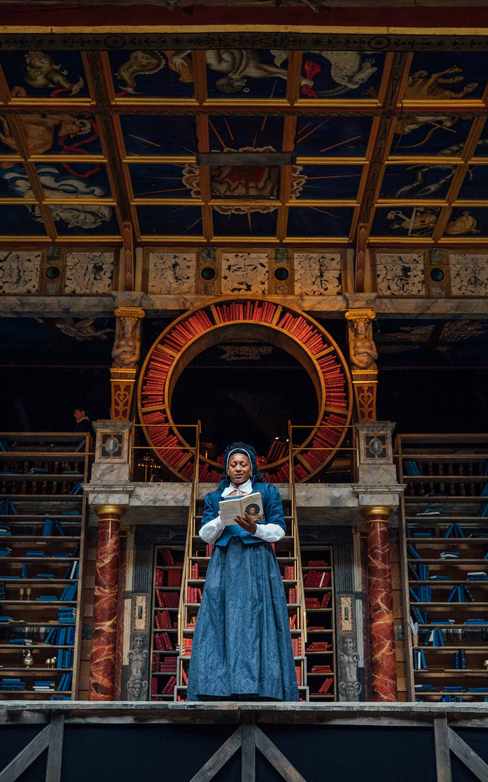 A woman wearing a blue Elizabethan corset dress stands on stage, reading a book, with shelves of bookcases behind her.