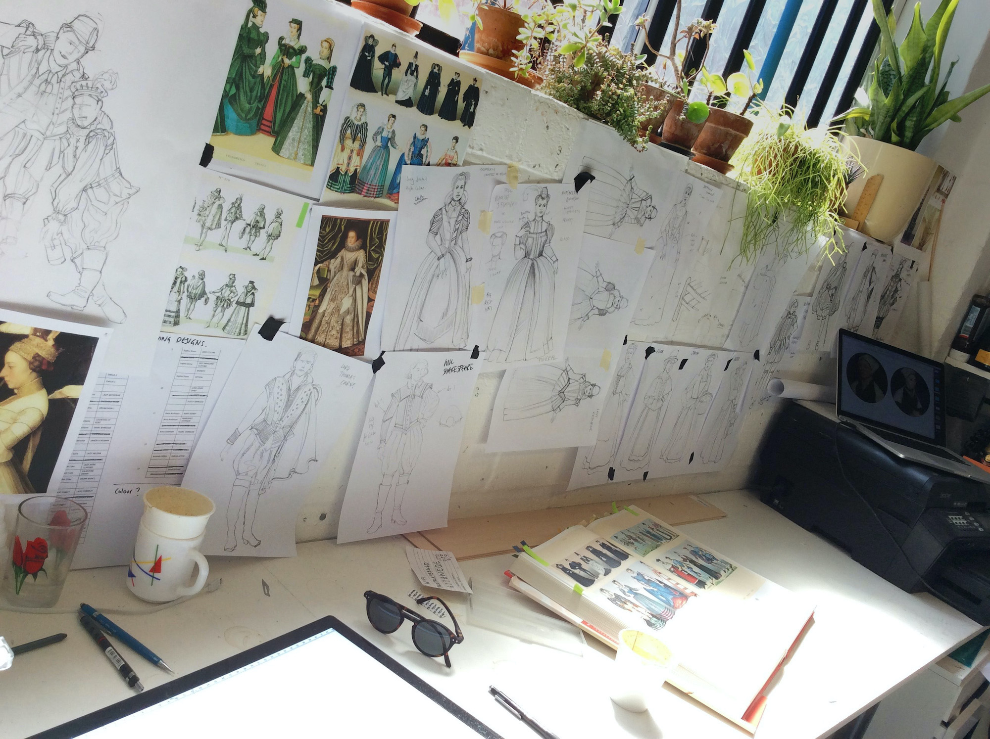 A photo of a designer's desk shows sketches, a sketch book, a mug, a glass and pens