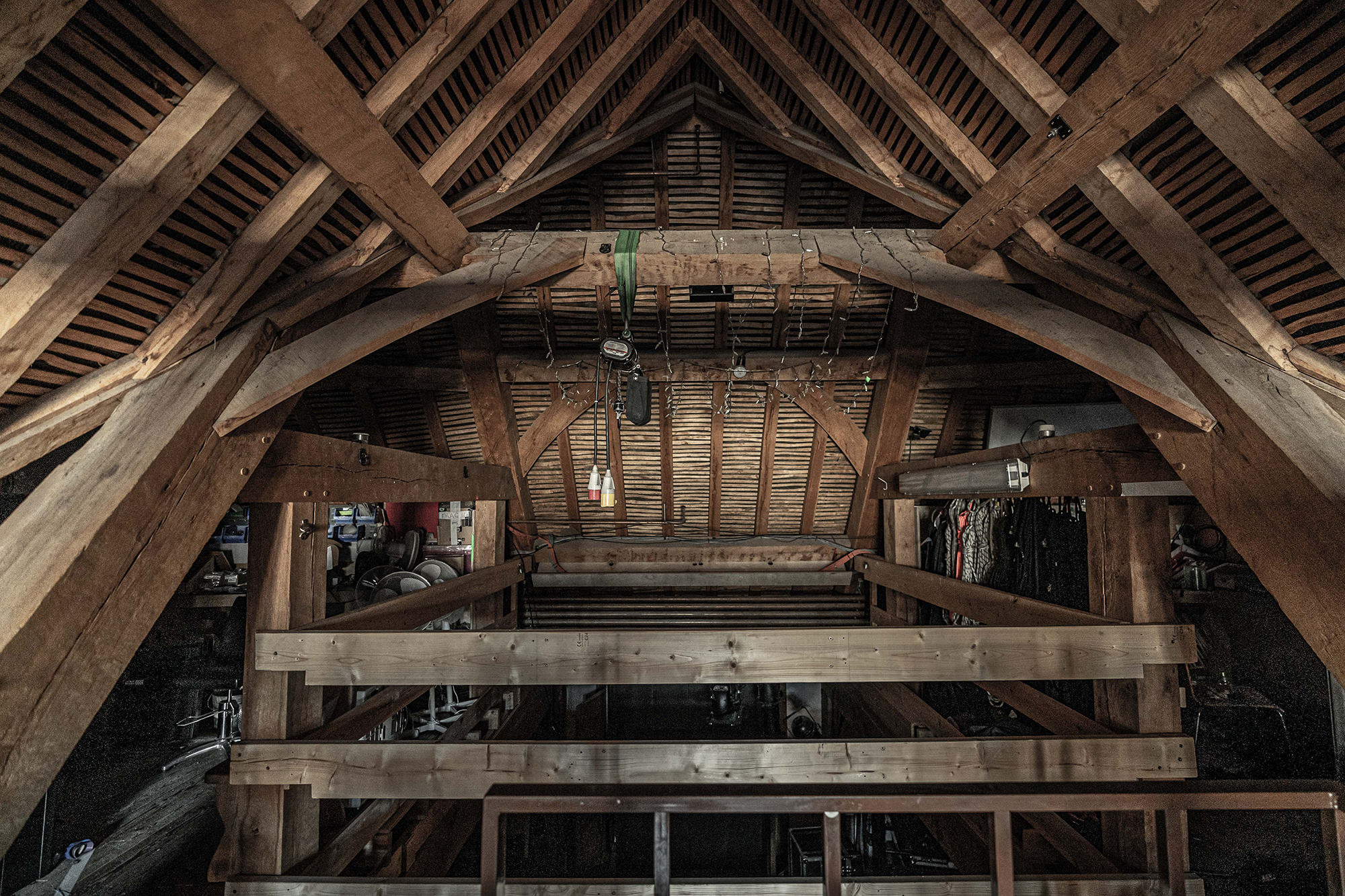 The inside of an attic with thatch roof and great oak beams. Various cables and objects hang from the rafters.