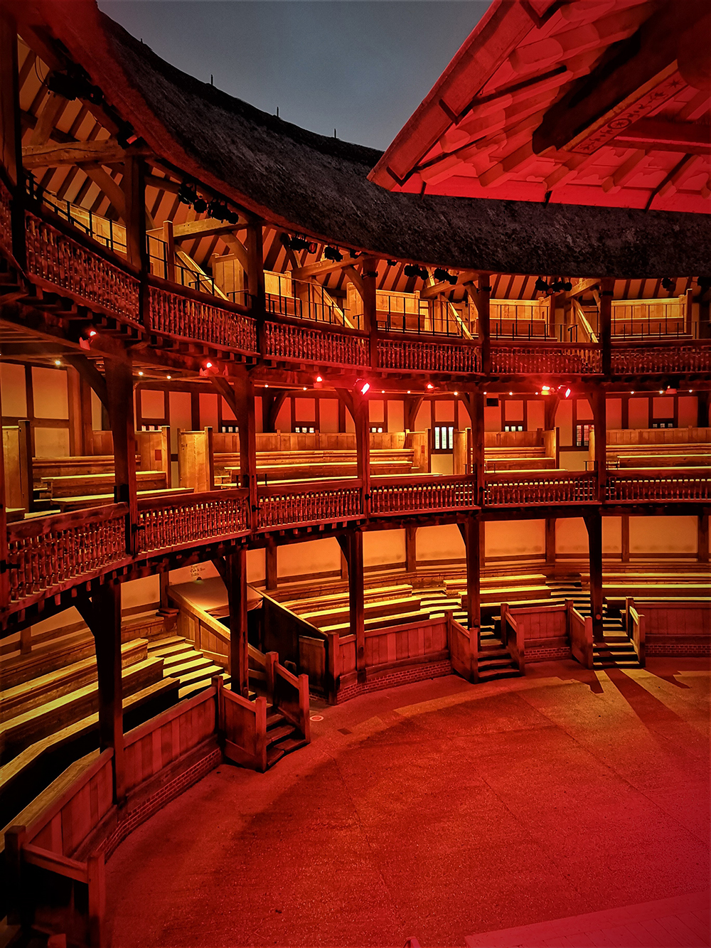 The inside galleries of the Globe Theatre are bathed in a red light.