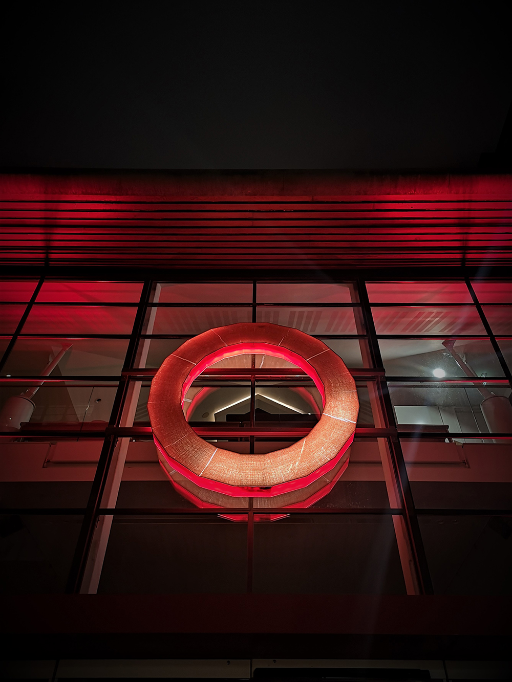 The red circular logo of Shakespeare's Globe is backlit by red light.