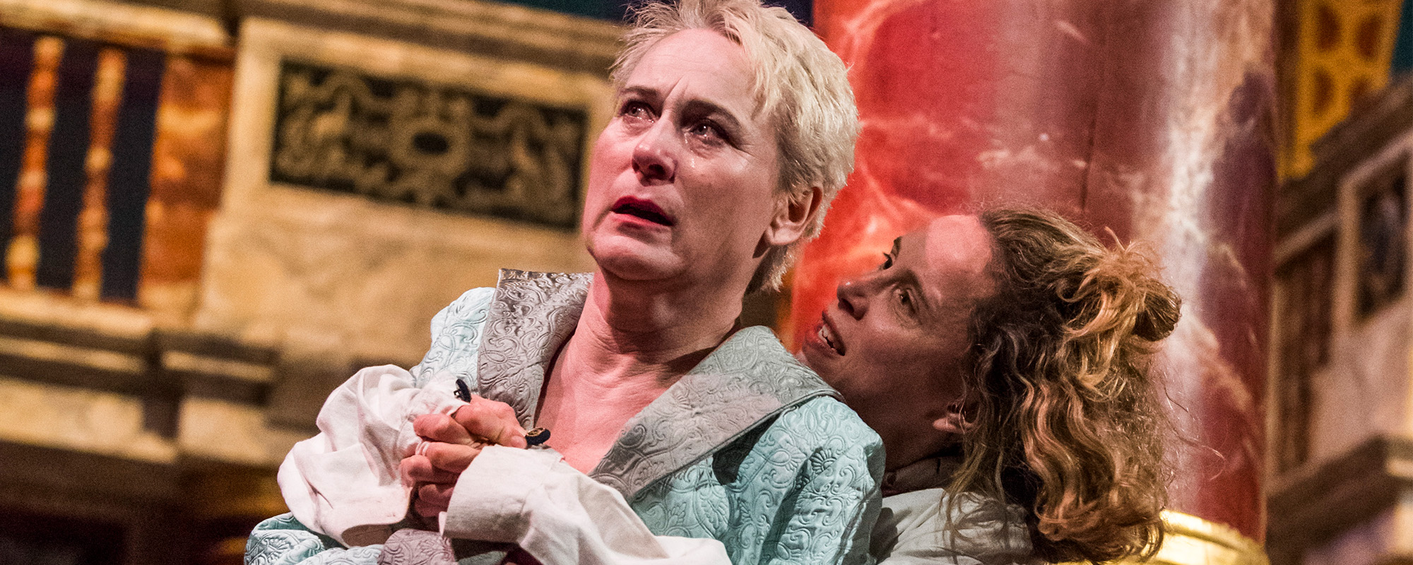 An actor looks distressed on the globe stage while another actor wrap their arms round them in a sinister hug