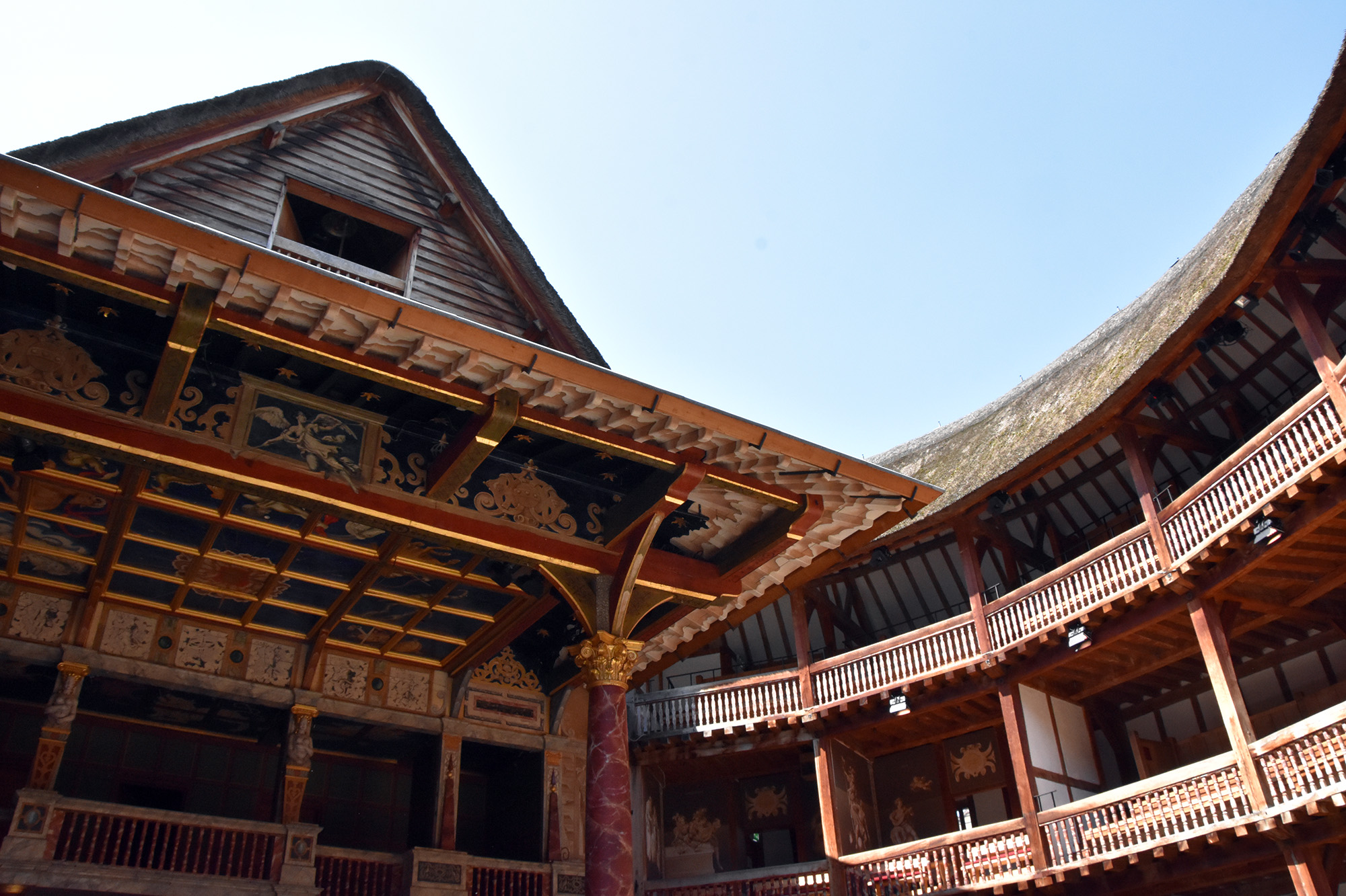 A soft blue sky shines above the inside of the Globe Theatre, casting light on the wooden galleries.