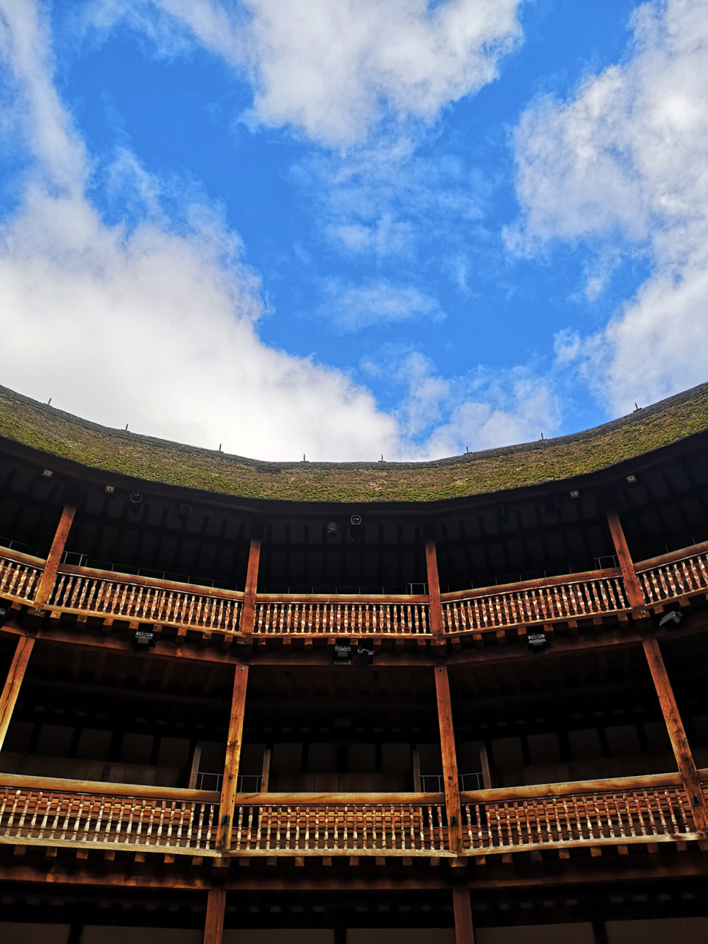 A bright blue sky, with streaks of clouds, above the timber tiered galleries of the Globe Theatre.