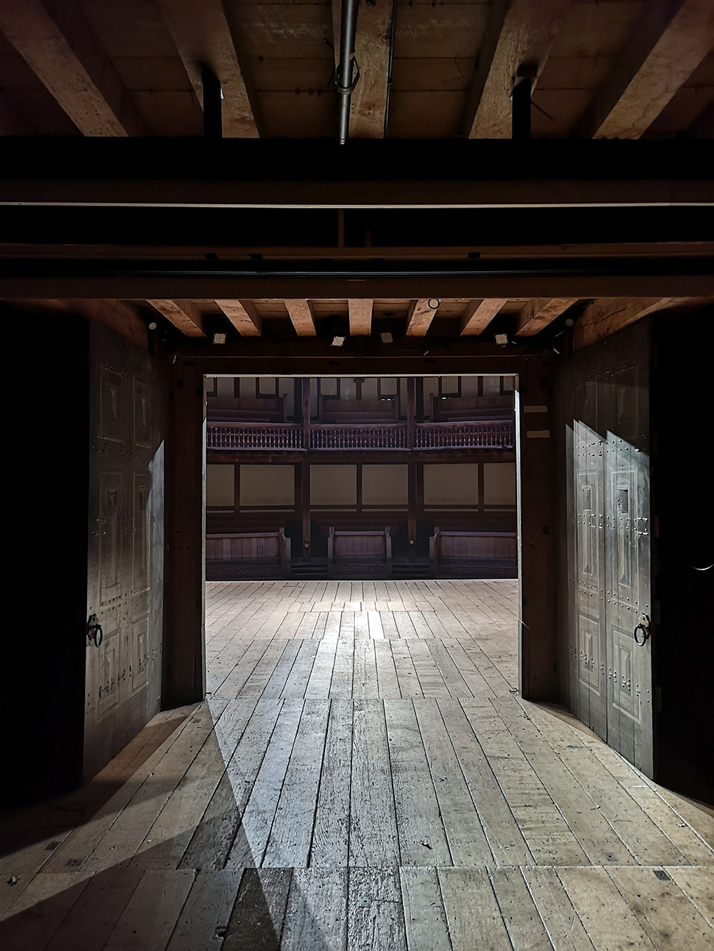 A view from backstage of the Globe Theatre, looking out through the open double oak doors on to the stage and the galleries beyond.