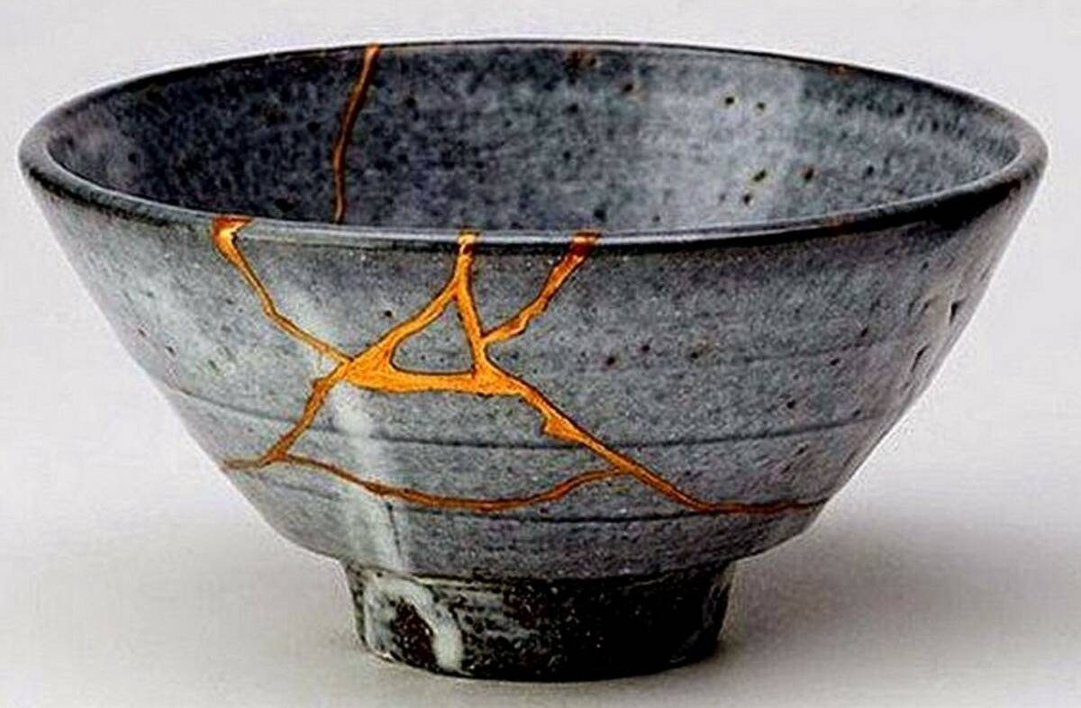 A grey speckled bowl that has been cracked and repaired with golden lacquer.