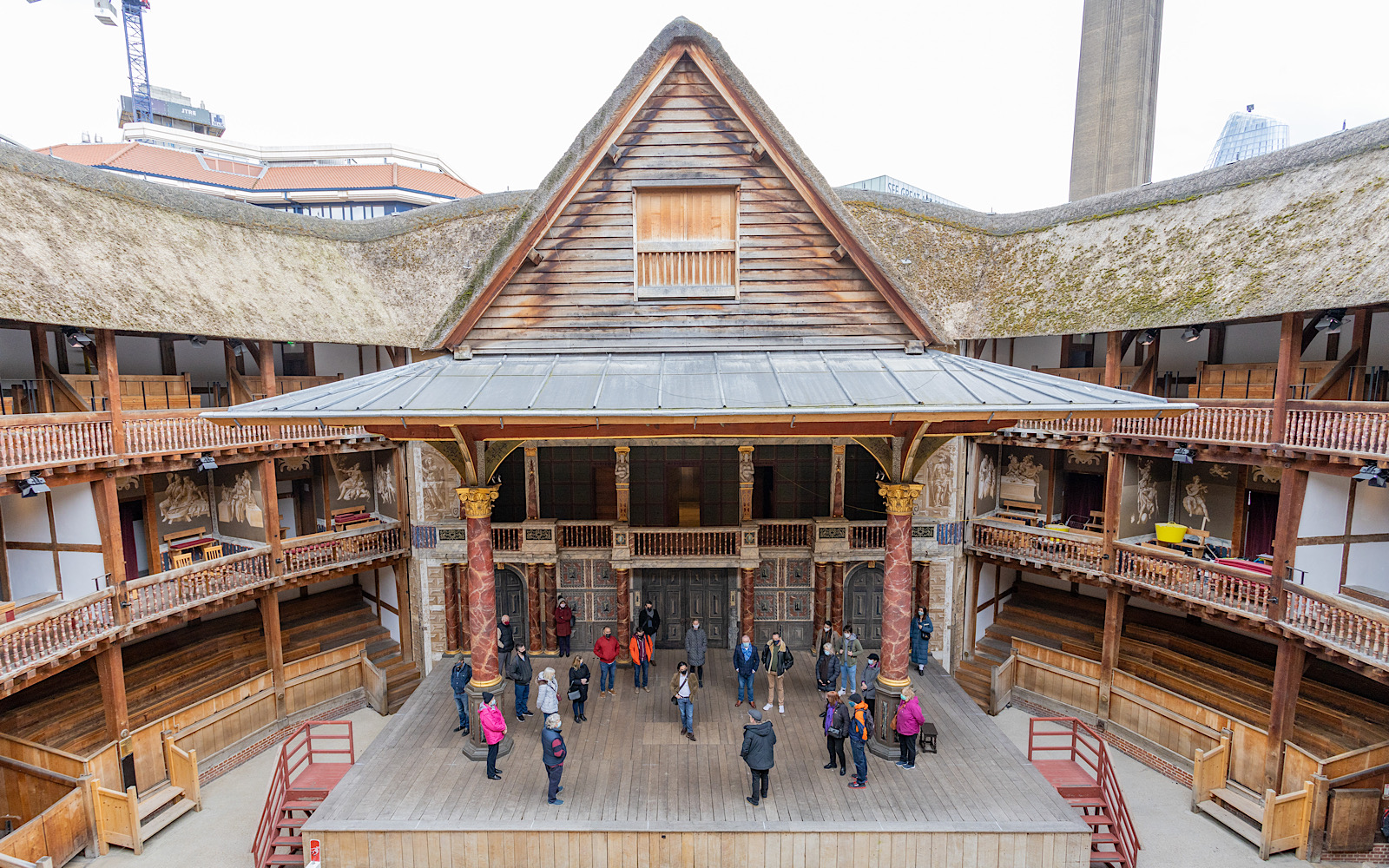 The Globe Theatre stage has a tall triangle roof and is held up by intricately decorated pillars